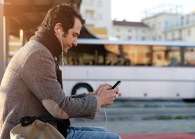 Passenger using his smartphone while waiting for the bus
